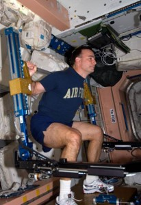 Astronaut Lee Archambault, commander of the STS-119 mission, conducts an Advanced Resistive Exercise Device (ARED) workout in the Unity node aboard the International Space Station. (NASA)