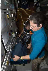 NASA astronaut Nicole Stott, STS-133 mission specialist, using a camcorder to record Mouse Immunology-2 investigation in one of the space shuttle Discovery's middeck lockers. (NASA)