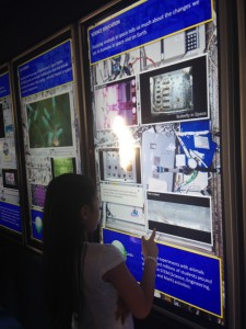 A young visitor to the NASA mobile exhibit interacts with a display of a research rack as it would appear aboard the International Space Station. (Tara Ruttley)