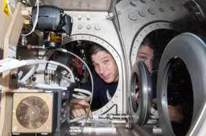 Expedition 38 Flight Engineer Mike Hopkins of NASA sets up the Microgravity Science Glovebox (MSG) for the Burning and Suppression of Solids (BASS-II) investigation in the Destiny laboratory of the International Space Station. BASS-II explores how different substances burn in microgravity with benefits for combustion on Earth and fire safety in space. (NASA)