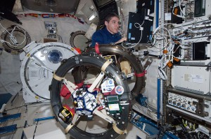 NASA astronaut Michael Hopkins works with the Department of Defense Synchronized Position, Hold, Engage, Reorient, Experimental Satellites-Resonant Inductive Near-field Generation System (DOD SPHERES-RINGS). (NASA)