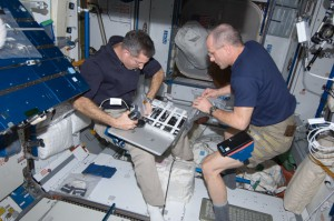 Expedition 30 Commander Dan Burbank (left) and Flight Engineer Don Pettit of NASA stow camera equipment in a container in the Harmony node of the International Space Station. (NASA)
