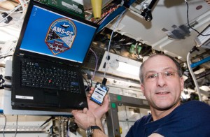 View of Don Pettit, Expedition 30 Flight Engineer, holding the Alpha Magnetic Spectrometer (AMS) laptop in the U.S. Laboratory of the International Space Station. (NASA)