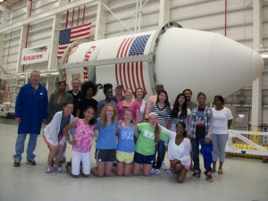 "SSEP Mission 5 launch delegation posing in from of the Antares rocket that successfully carried the selected experiment 'Oxidation in Space"" to the International Space Station in July 2014. (aSTEAM Village)"