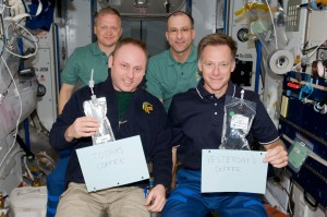 In 2008, astronauts aboard the International Space Station demonstrated the pouch method of drinking yesterday's coffee and today's coffee, while the Space Cup will serve the coffee of tomorrow — providing real science for fluid physics research. In the front, left to right, crew members Michael Finke and Chris Ferguson, with Eric Boe and Donald Pettit in the back. (NASA)