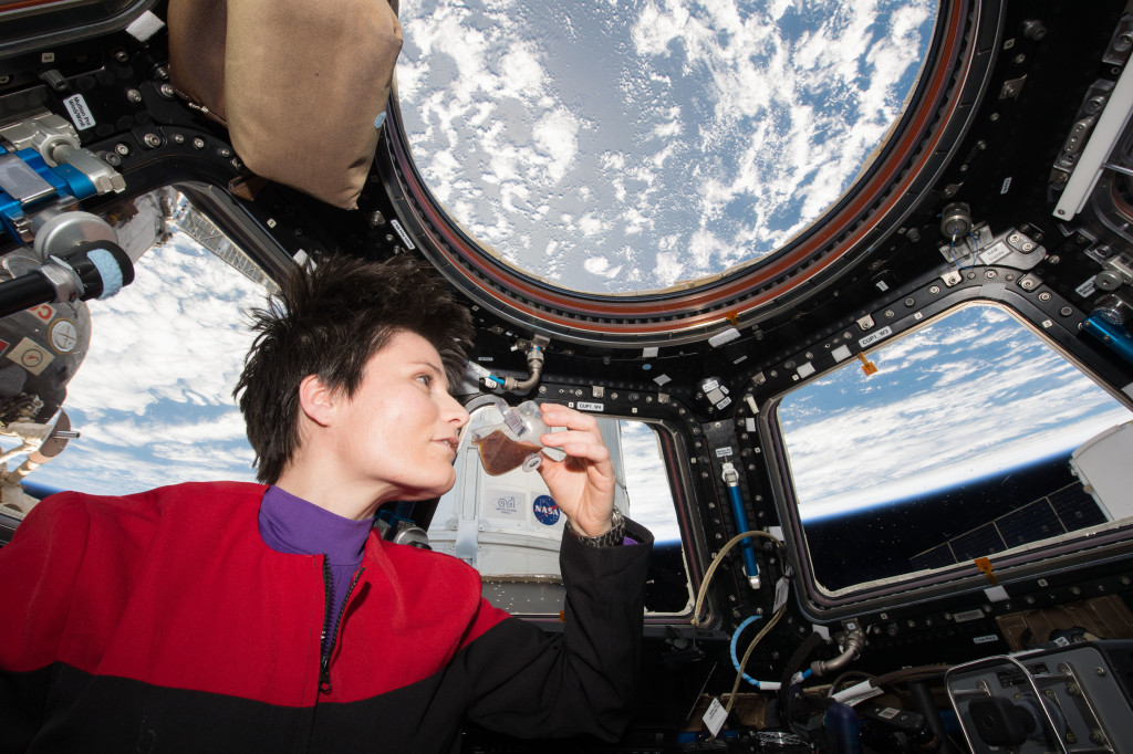 SA (European Space Agency) astronaut Samantha Cristoforetti - dressed in a Star Trek Voyager uniform - takes a sip of espresso from the new Capillary Beverage investigation, also known as Space Cup while looking out of the Cupola window.