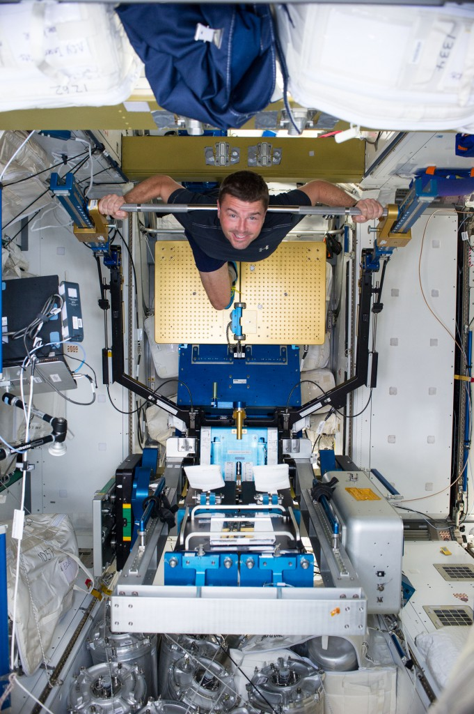 NASA astronaut Reid Wiseman, Expedition 40 flight engineer, gets a workout on the Advanced Resistive Exercise Device (ARED) in the Tranquility node of the International Space Station. (NASA)