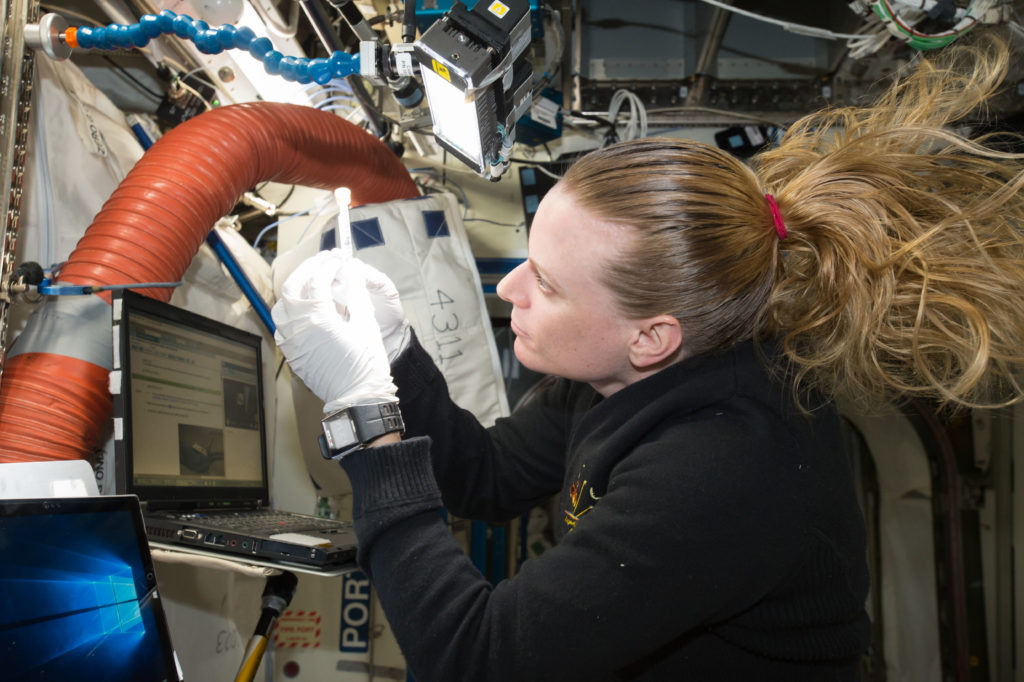 NASA astronaut Kate Rubins checks a sample for air bubbles prior to loading it in the biomolecule sequencer. Credits: NASA