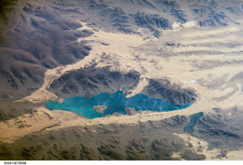 Har (or Black) Lake is located in the western part of Mongolia within the Valley of Lakes--part of a system of closed basins that stretches across central Asia. This oblique view captures the dynamic nature of the landscape of Har Lake. The lake is encircled by sand dune fields which encroach on the lower slopes of the Tobhata Mountains to the west and south. This image was captured on Sept. 15, 2006.