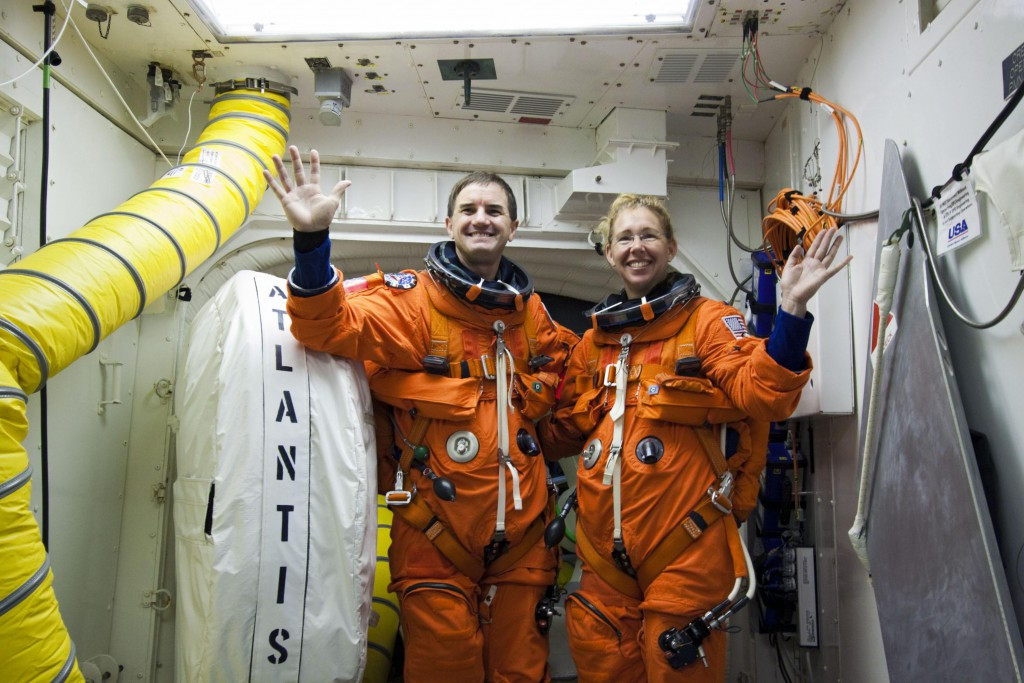 STS-135 crew members Rex Walheim and Sandy Magnus at the hatch to Atlantis