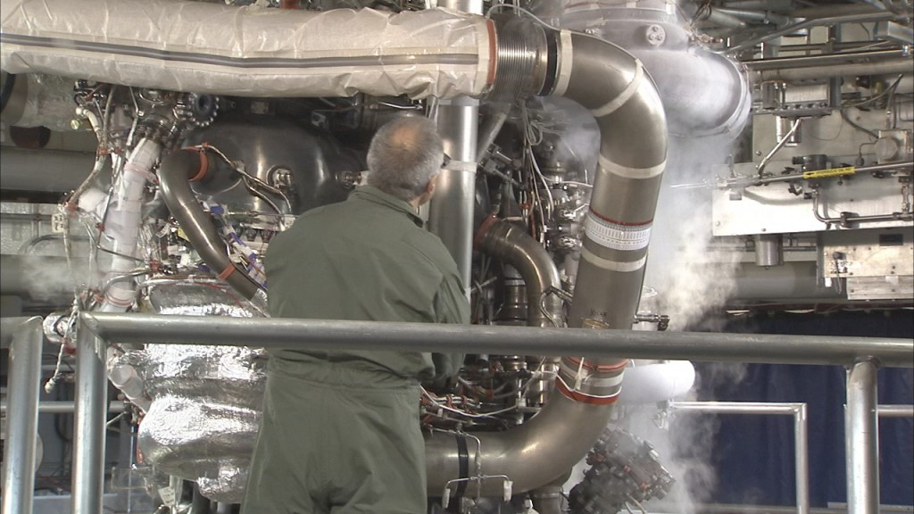 A worker inspects the machinery of an RS-25 engine