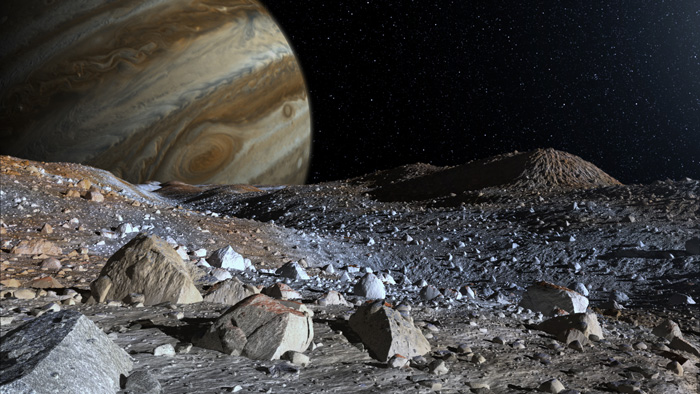 Jupiter hangs in the sky above the surface of a moon