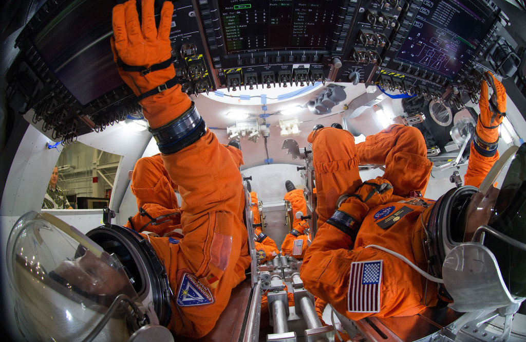 Spacesuit engineers demonstrate how four crew members would be arranged for launch inside the Orion spacecraft, using a mockup of the vehicle at Johnson Space Center.