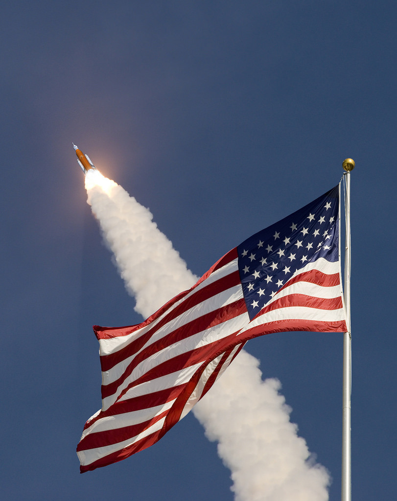 Artist concept of an American flag in front of an SLS launch
