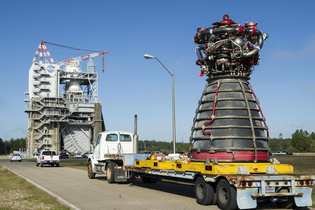 An RS-25 engine is delivered by flatbed truck to a test stand at Stennis Space Center.