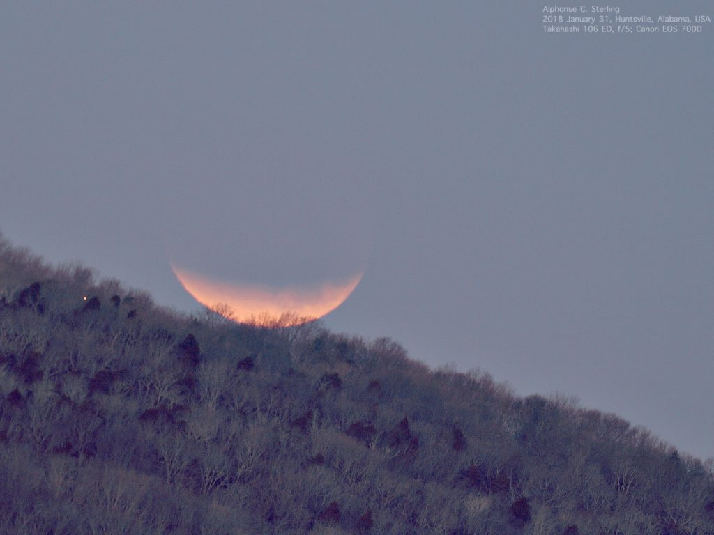 The Moon is seen here during the January 2018 lunar eclipse, setting in the western horizon, not yet in totality.