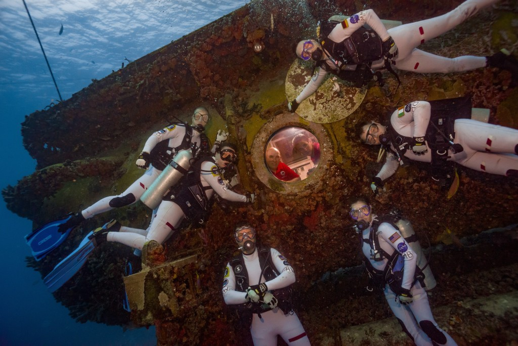 Pictured at the end of Mission Day 1 are the NEEMO 21 aquanauts, clockwise from top: Matthias Maurer (ESA), Marc O Griofa (Teloregen/VEGA/AirDocs), NASA astronaut Megan McArthur, NASA astronaut Reid Wiseman, Dawn Kernagis (Institute for Human & Machine Cognition), and Noel Du Toit (Naval Postgraduate School). Inside the Aquarius habitat are Florida International University Habitat Technicians Hank Stark (left) and Sean Moore (right).