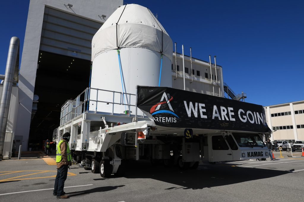Orion is buttoned up and ready to march towards the Multi-Payload Processing Facility to begin ground processing by the Exploration Ground Systems and Jacobs teams ahead of the Artemis I launch. Shielded by a protective covering for transport, the spacecraft departs its home at the Neil Armstrong Operations and Checkout Building at NASA's Kennedy Space Center in Florida on Jan. 16, 2021.