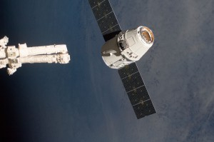 A SpaceX Dragon capsule is grappled by the International Space Station.