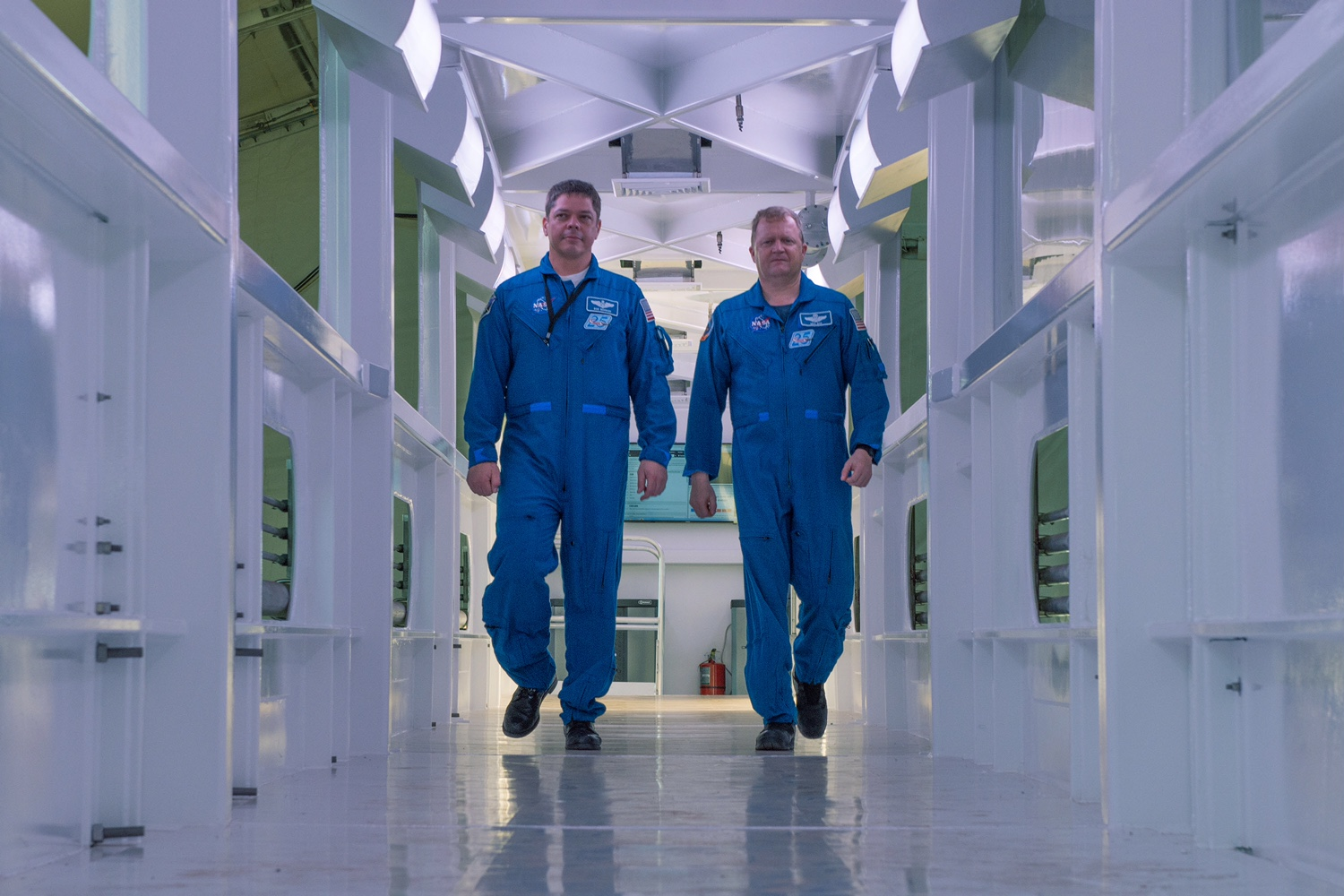 Astronauts Bob Behnken and Eric Boe walk down the Crew Access Arm being built by SpaceX for Launch Complex 39A at NASA's Kennedy Space Center in Florida