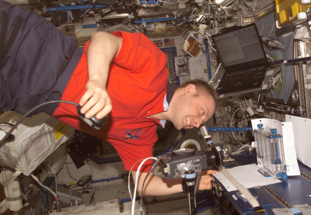 Astronaut Edward M. (Mike) Fincke, Expedition 9 NASA ISS science officer and flight engineer, performs one of multiple tests of the Capillary Flow Experiment investigation in the Destiny laboratory of the International Space Station in September 2004.