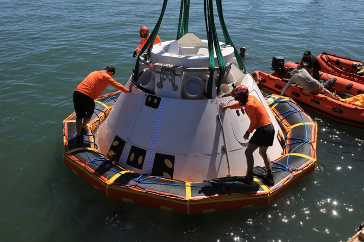 Rescue team members stand on the stabilization collar attached to the Boeing CST-100 Starliner training capsule, known as Boiler Plate 3, during a search and rescue training exercise April 16, 2019.