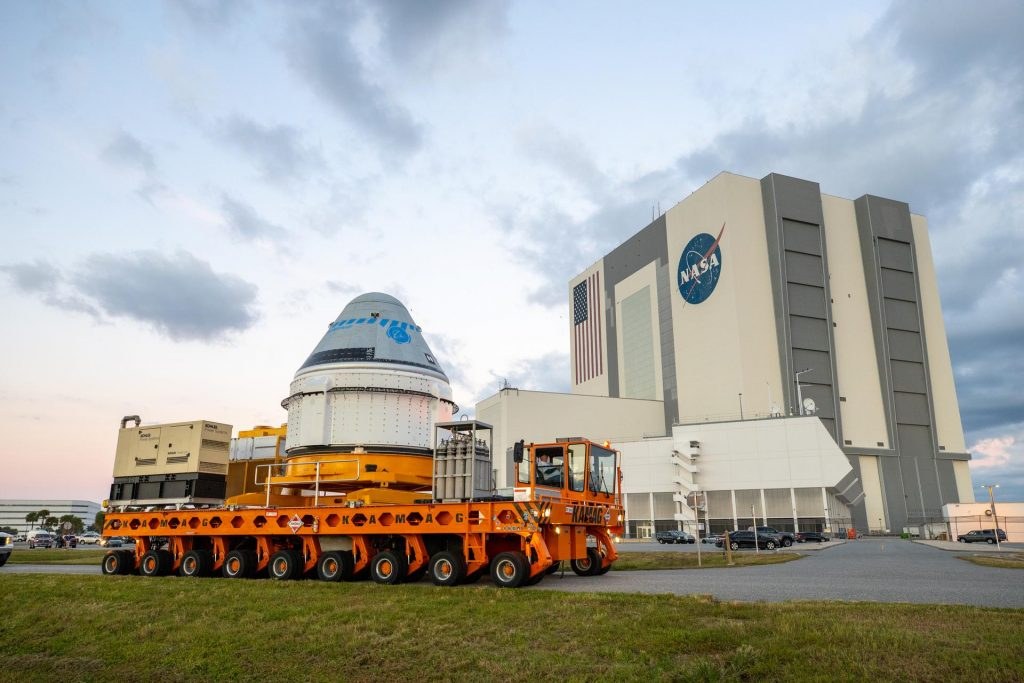 Boeing's CST-100 Starliner spacecraft passes by the Vehicle Assembly Building at NASA's Kennedy Space Center in Florida on Thursday, Nov. 21, on its way to Space Launch Complex 41 Vertical Integration Facility.