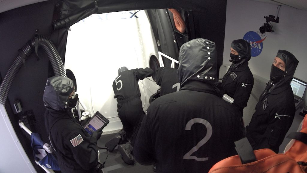 SpaceX technicians in the White Room at Launch Complex 39A close the Crew Dragon's side hatch and check for leaks.