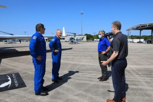 Demo-2 crew members Robert Behnken (far left) and Douglas Hurley are greeted by NASA Administrator Jim Bridenstine (far right) Kennedy Space Center Director Bob Cabana at the Launch and Landing Facility runway.