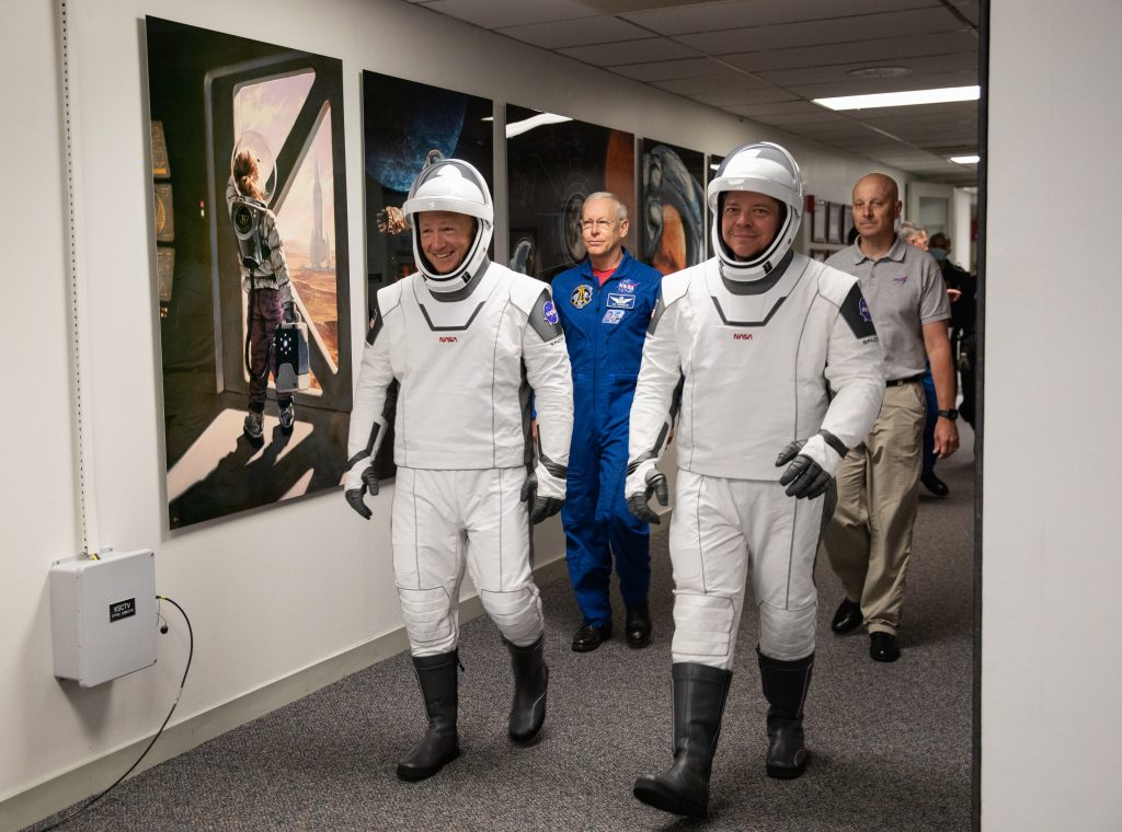 Demo-2 crew members Robert Behnken (right) and Douglas Hurley walk down the hallway of the Neil A. Armstrong Operations and Checkout Building at the Kennedy Space Center in Florida during a dry dress rehearsal ahead of NASA's SpaceX Demo-2 launch.