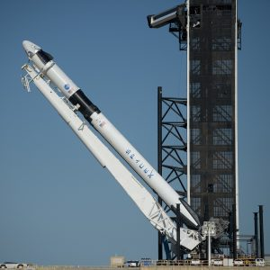 A SpaceX Falcon 9 rocket with the company's Crew Dragon spacecraft onboard is seen as it is raised into a vertical position on the launch pad at Launch Complex 39A.