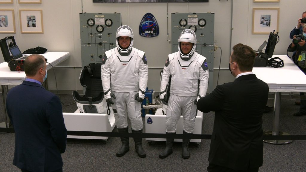 NASA astronauts Robert Behnken, left, and Douglas Hurley talk to NASA Administrator Jim Bridenstine, far left, and SpaceX's Elon Musk inside the suit room in Kennedy Space Center's Neil Armstrong Operations and Checkout Building.