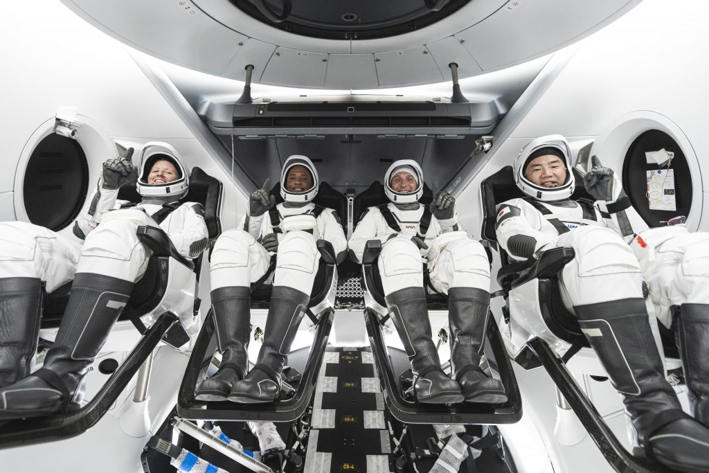 NASA's SpaceX Crew-1 crew members are seen seated in the company's Crew Dragon spacecraft during training. From left to right are NASA astronauts Shannon Walker, Victor Glover, and Mike Hopkins, and JAXA astronaut Soichi Noguchi. Photo credit: SpaceX