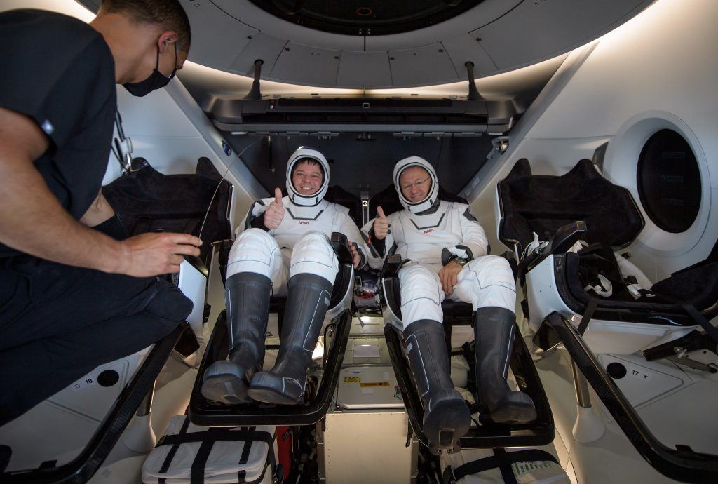 NASA astronauts Robert Behnken, left, and Douglas Hurley are seen inside the SpaceX Crew Dragon Endeavour spacecraft onboard the SpaceX GO Navigator recovery ship shortly after having landed in the Gulf of Mexico off the coast of Pensacola, Florida, Sunday, Aug. 2, 2020.