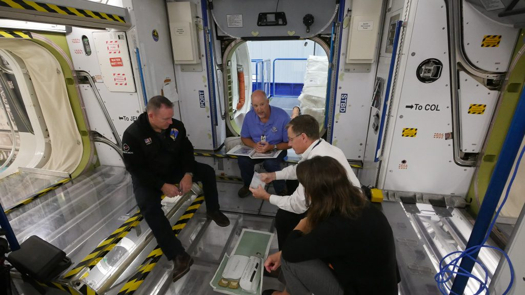 "NASA astronauts Nicole Mann and Barry ""Butch"" Wilmore and Boeing astronaut Chris Ferguson review International Space Station training at NASA's Johnson Space Center in Houston, Texas."