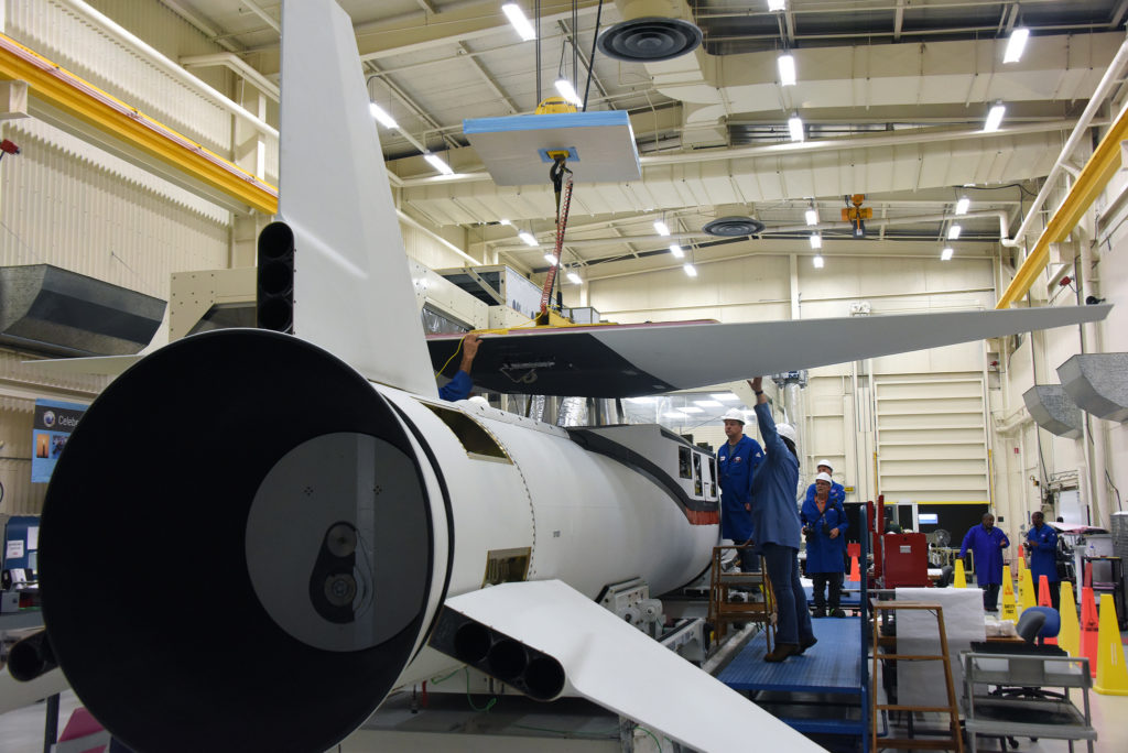 Technicians and engineers perform final wing installations on the Orbital ATK Pegasus XL rocket which will launch eight NASA Cyclone Global Navigation Satellite System, or CYGNSS, spacecraft.