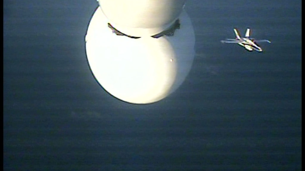 The chase plane is visible below the Pegasus XL rocket in this image from a camera mounted to the underside of the L-1011.