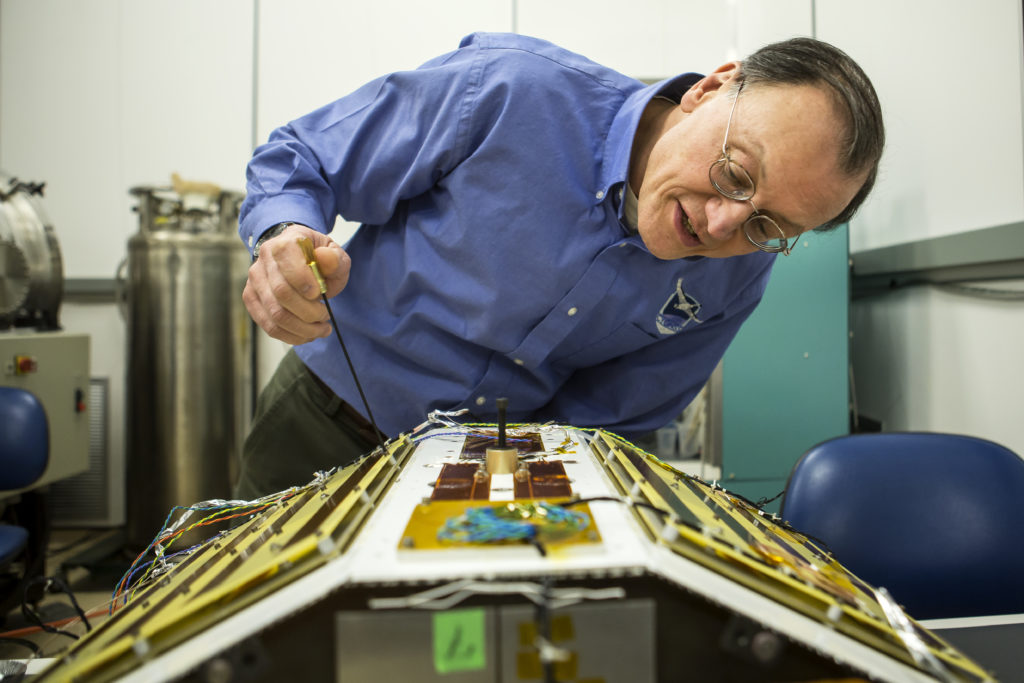 Principal Investigator Dr. Christopher Ruf inspects CYGNSS in the lab, February 2015.