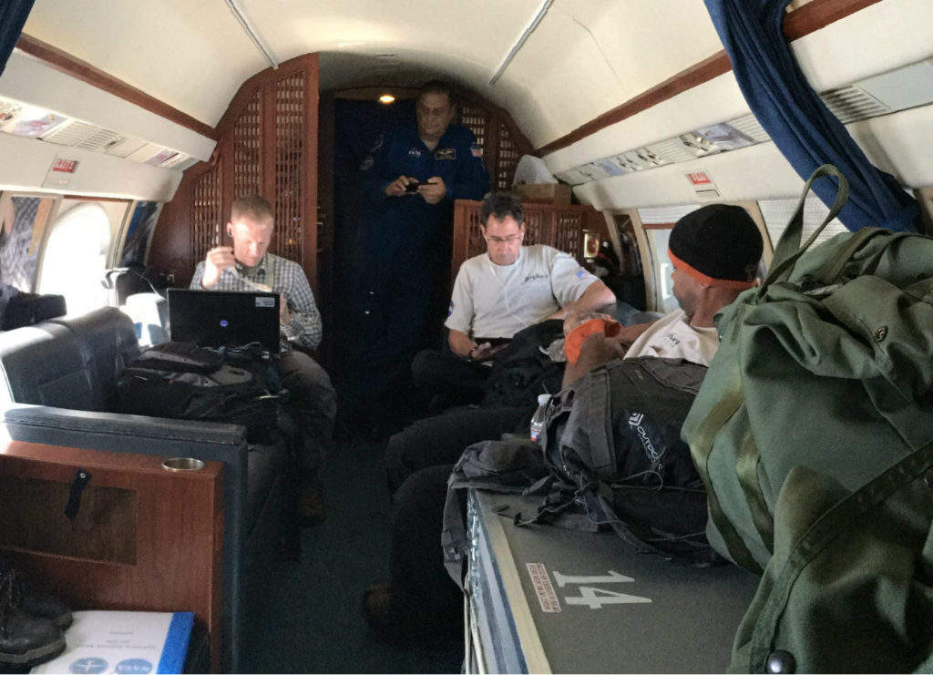The team relaxes in the plane during a lengthy transit flight. Credit: NASA/JPL-Caltech