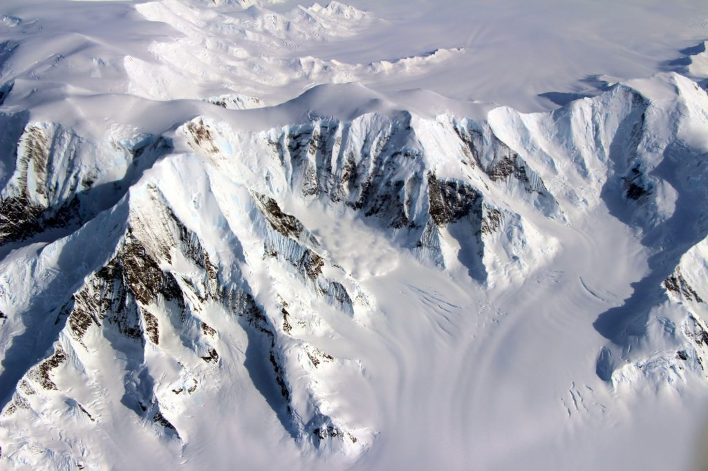 The Mountains of Alexander Island as seen from the NASA DC-8 on October 15, 2016.  The curious feature near the floor of the valley at center may be a small patch of fog, or it may be an avalanche in progress. Credit: NASA/John Sonntag