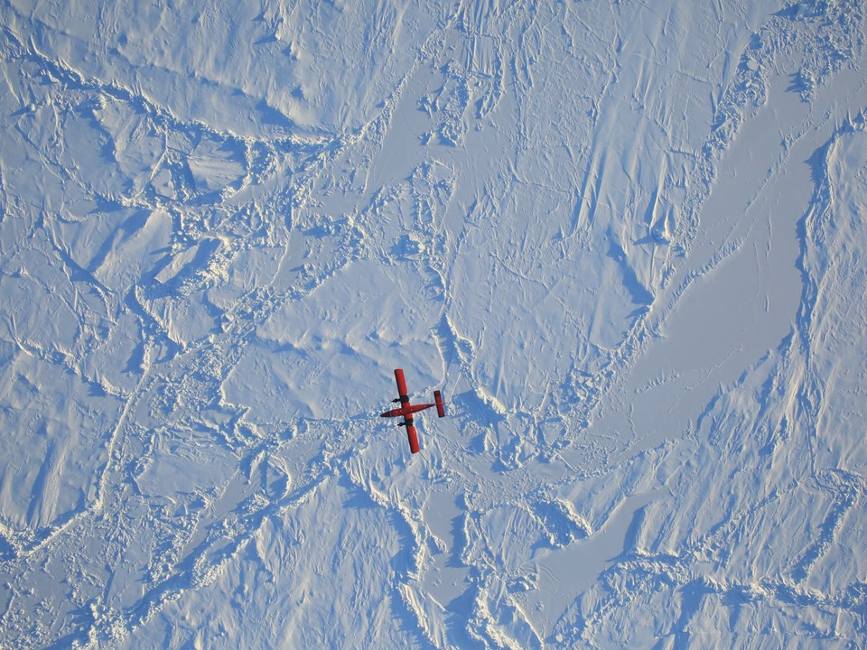 An image of ESA's Twin Otter passing underneath the P-3, captured by Operation IceBridge's high-resolution camera. Credit: NASA/Dennis Gearhart
