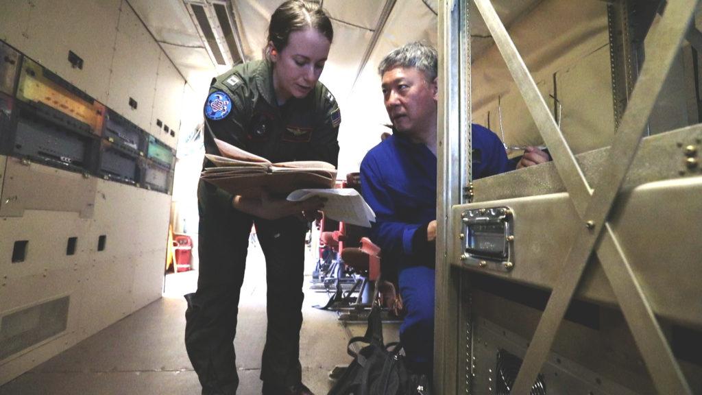 Lt. Denise Miller from the U.S. Navy speaks with Principle Investigator Edward Kim during a science flight. Credit: NASA/Joy Ng