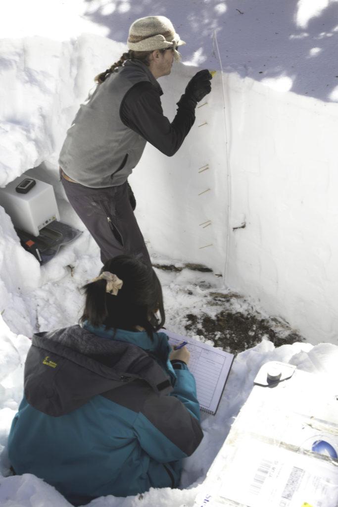 Travis Roth, Oregon State University looks at snow consistency at various depths as Jinmei Pan, Ohio State University logs data. Credit: Ryan Cook