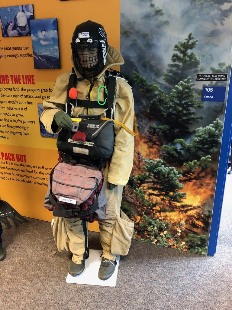 Smokejumpers wear Kevlar jump suits to avoid punctures from rocks and branches when they land in rough terrain. They also carry extra rope for getting out of trees. Credit: NASA