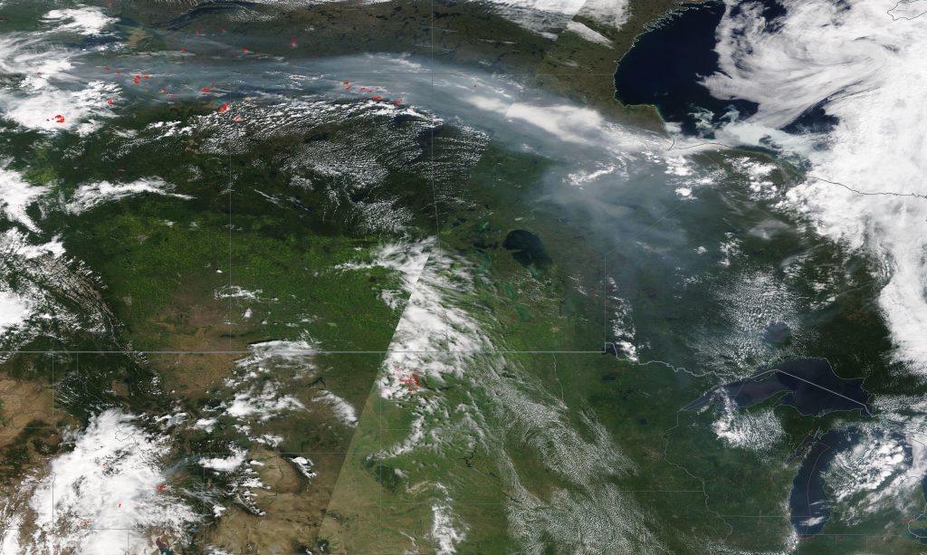 True color satellite image of Canada and the northern United States on July 23, 2019. Fires in northern Alberta (red dots in top left) produced smoke that traveled to the Great Lakes (bottom right) over the course of a few days. Credit: NASA EOSDIS / Worldview
