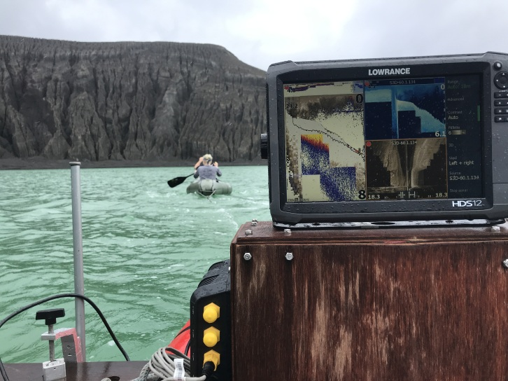 Collecting a side-scan sonar transect of the crater lake. The Lowrance is in the foreground, with Cam and Grace towing it in another inflatable raft. The crater wall is also in the background. Credit: SEA