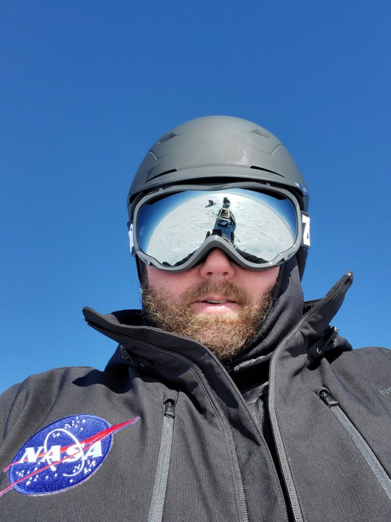 "SnowEx 2020 operations manager Jerry Newlin (ATA Aerospace) caught Chris Hiemstra (U.S. Army Corps of Engineers' Cold Regions Research and Engineering Laboratory) in the reflection of his goggles during one of their daily snowmobile commutes. ""It looks like Chris is collecting data on the Moon,"" Newlin said. Credit: NASA / Jerry Newlin"