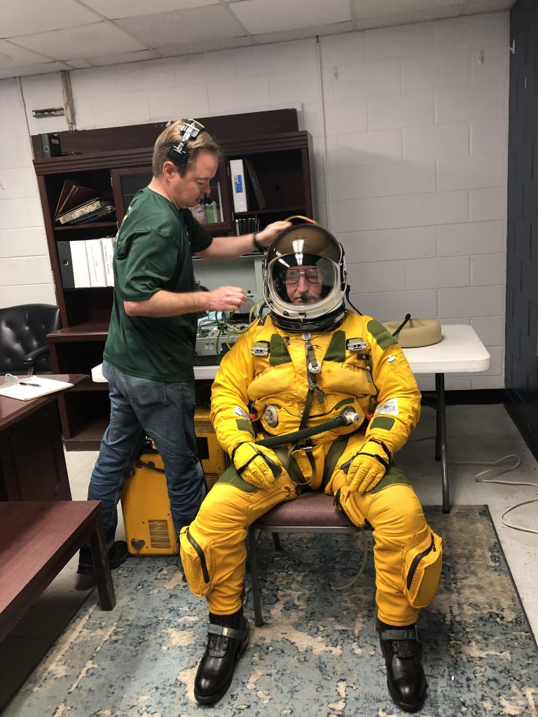 Joey Barr making sure that Cory Bartholomew is happy with his glasses. Once the helmet is shut, the pilot will not open the visor again until after landing. Credit: NASA/Katie Stern