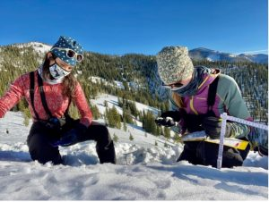 The author and another research assistant, Megan Mason, identify snow crystal types in an early-season snow pit at Copper Mountain, Idaho, December 2020. Credit: G. Antonioli