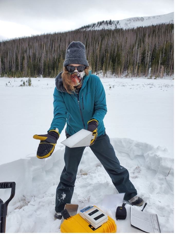 A scientist shows off a sample of a snow pit to measure snow density.